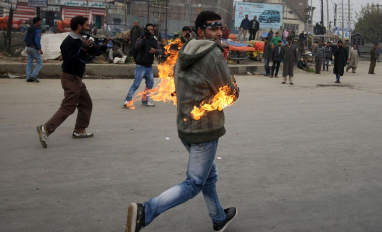 A Kashmiri Shitte muslim runs after setting his hand on fire during a clash with Indian police in Srinagar on November 23, 2012, as devotees defy restrictions for a Muharram procession. Authorities imposed restrictions in parts of Srinagar, the summer capital of Kashmir, to thwart planned Muharram processions as police detained more than a dozen protesters and fired teargas to disperse participants. (STR/AFP/Getty Images)