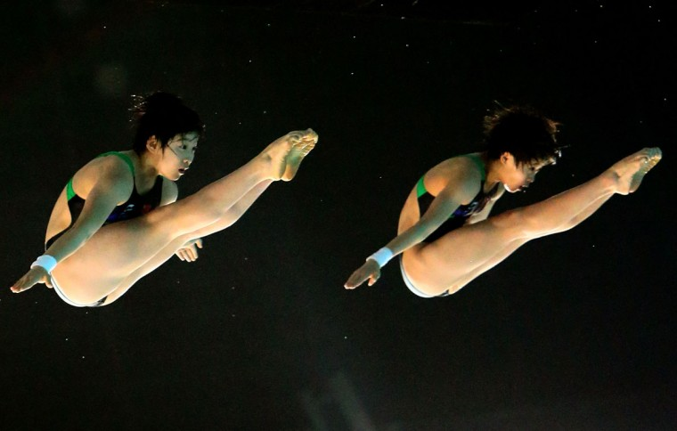 Xing Yiying and Wang Wenna of China dive to win the gold medal in the women's syncronised 10m platform during the 9th Asian Swimming Championships in Dubai. (Marwan Naamani/AFP/Getty Images)