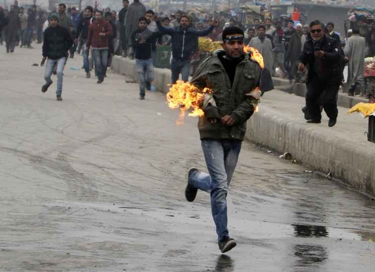 A Kashmiri Shitte muslim runs after setting his hand on fire during a clash with Indian police in Srinagar as devotees defy restrictions for a Muharram procession. Authorities imposed restrictions in parts of Srinagar, the summer capital of Kashmir, to thwart planned Muharram processions as police detained more than a dozen protesters and fired teargas to disperse participants. (STR/AFP/Getty Images)