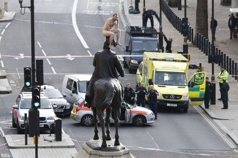 An unidentified man sits naked on top of the statue of Prince George, Duke of Cambridge outside the Ministry of Defence building in Whitehall in central London. The man, who brought Whitehall to a standstill for almost two hours, stood naked on the statue and struck various poses before being eventually talked down. (Justin Tallis/AFP/Getty Images)