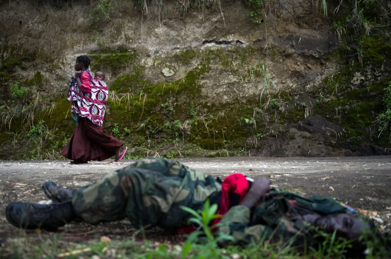A Congolese lady carrying her child walks past a dead soldier on the road from Sake towards Minova in the east of the Democratic Republic of the Congo. Fresh fighting yesterday between M23 rebels and government troops in Sake caused tens of thousands to flee the area yesterday, taking refuge in Mugunga. (Phil Moore/AFP/Getty Images)