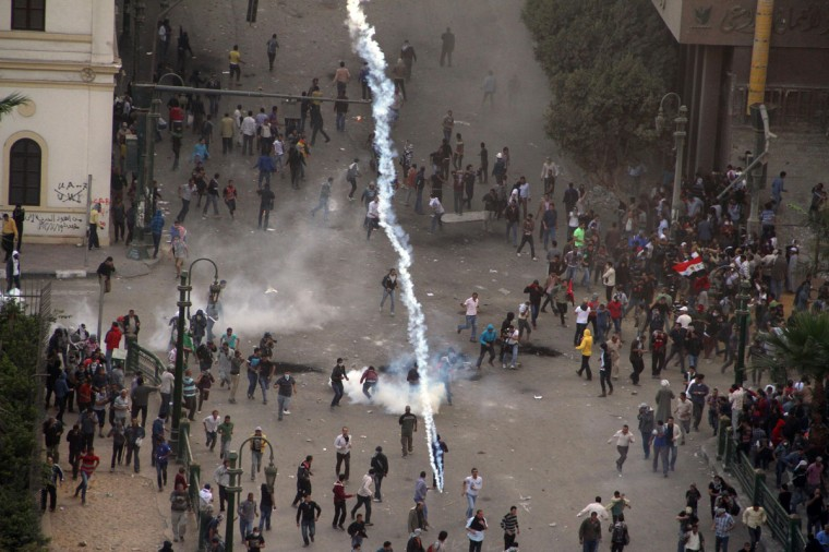 Protesters demonstrating against Egypt's Islamist President Mohamed Morsi run from tear gas fired by Egyptian riot police during clashes in Cairo's landmark Tahrir square on November 23, 2012. (Ahmed Mahmoud/AFP/Getty Images)