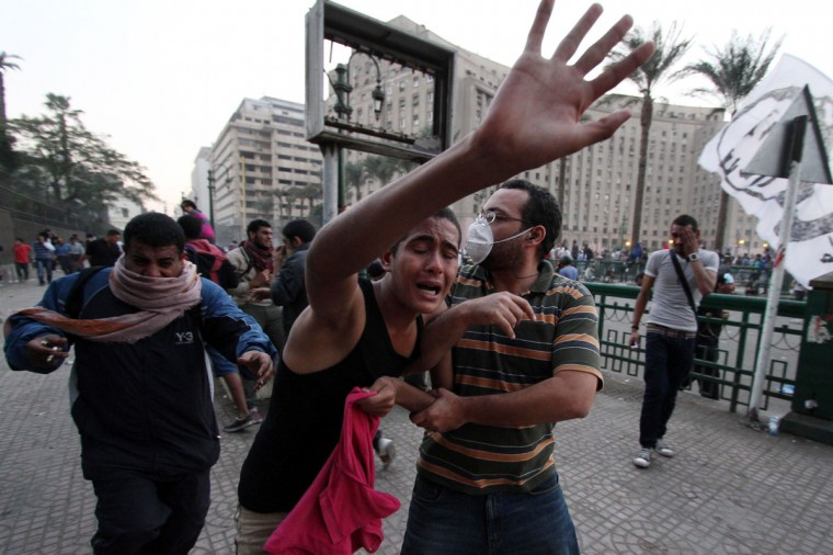 Protesters run for cover as they suffer from tear gas inhalation from canisters fired by Egyptian riot police during clashes following a demonstration against Egypt's Islamist President Mohamed Morsi in Cairo's landmark Tahrir square on November 23, 2012. (Ahmed Mahmoud/AFP/Getty Images)