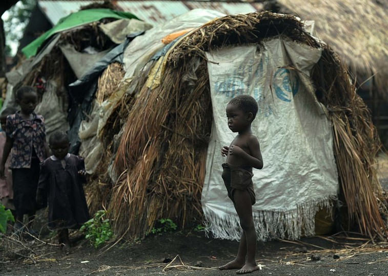 A displaced young Congolese boy stands outside his family's ramshackle shelter during a food aid distribution exercise conducted by humanitarian agencies at a camp for the internally displaced in Mugunga on November 24, 2012. Thousands of people have been displaced due to fighting between M23 rebels and government forces in eastern D.R. Congo's North Kivu region. (Tony Karumba/AFP/Getty Images)