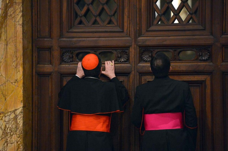 Italian cardinal Giuseppe Betori (L) and a bishop take a glimpse through a door during the courtesy visit to the cardinals on November 24, 2012 at the Apostolico palace at the Vatican. Six non-European prelates are set to join the Catholic Church's College of Cardinals, a move welcomed by critics concerned that the body which will elect the future pope is too Eurocentric. (Vincenzo Pinto/AFP/Getty Images)