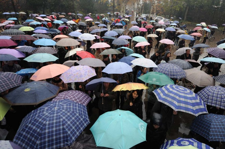 A group of candidates wait for the National Public Servant Exam in the rain at a university in Hefei, central China's Anhui province on November 25, 2012. More than 1.5 million people applied to take the exam, over 30 times the number a decade ago, vying for about 20,000 government vacancies, state media reported. (STR/AFP/Getty Images)