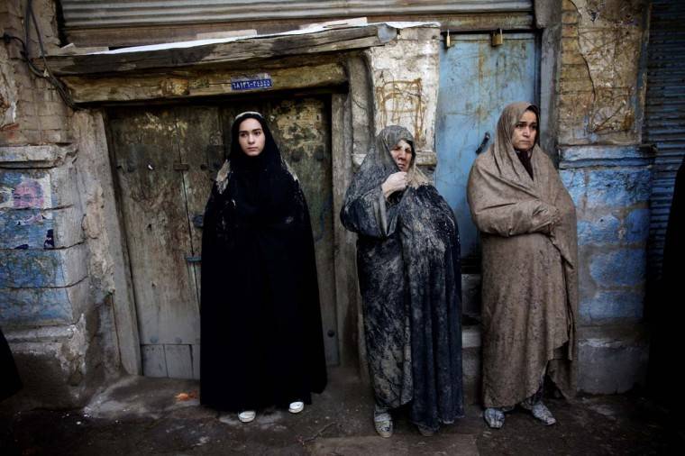 "Iranian Shi'ite Muslim women with mud on their veils watch the 'Kharrah Mali' (Mud Rubbing) ritual to mark the Ashura religious ceremony in the city of Khorramabad, southwest of Tehran on November 25, 2012. ""Khrreh Mali"" or ""Mud Rubbing"" is a ritual that is held in the city of Khorramabad every year to commemorate the seventh century slaying of Prophet Mohammed's grandson Imam Hussein, in which Iranian men roll over in mud and dry themselves by gathering around the bonfires before flagellating themselves. (Behrouz Mehri/AFP/Getty Images)"