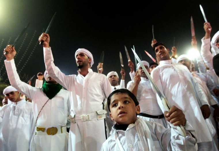 Shi'ite Muslims raise their swords outside the shrine of Imam Abbas early on November 25, 2012 in Karbala during the celebration of Ashura. (Ahmad Al-Rubaye/AFP/Getty Images)