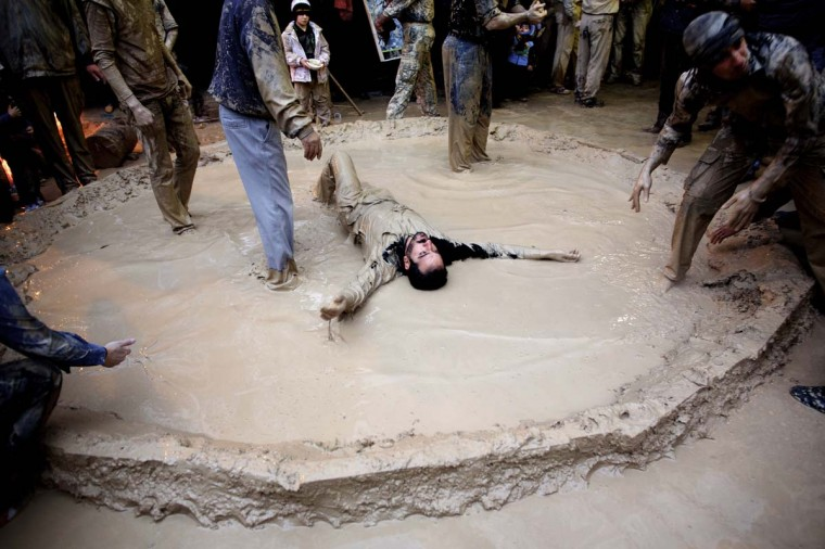 An Iranian Shi'ite Muslim rolls over in a mud pond early in the morning during the 'Kharrah Mali' (Mud Rubbing) ritual to mark the Ashura religious ceremony in the city of Khorramabad, southwest of Tehran on November 25, 2012. (Behrouz Mehri/AFP/Getty Images)