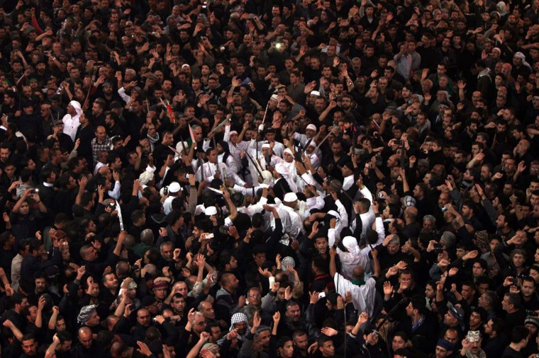 Shiite Muslims gather at the shrine of Imam Hussein early on November 25, 2012 in Karbala during the celebration of Ashura. Millions of pilgrims pour into the Iraqi shrine city of Karbala for the peak of commemorations for Ashura today, the most important day in the Shiite calendar, with security tight following mass-casualty attacks in previous years. (Ahmad Al-Rubaye/AFP/Getty Images)