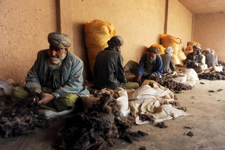 Afghan men work in a traditional wool factory in Herat on November 26, 2012. About 100 women and men work in the wool factory and receive about 4 to 6 USD per day. (Aref Karimi/AFP/Getty Images)