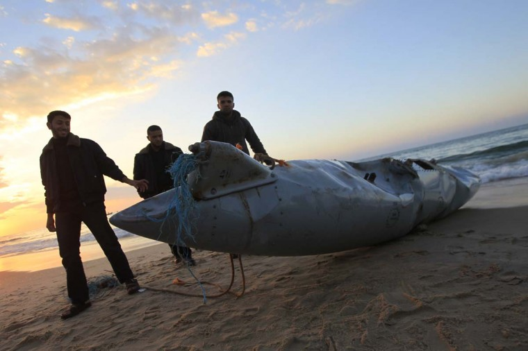 Members of the Hamas-run security forces inspect what appears to be part of an aircraft which washed ashore near Rafah in the southern Gaza Strip on November 26, 2012. Hamas media outlets claimed it was part of an Israeli plane brought down by militants, but there were no identifying marks on the wreckage which could corroborate the allegation that it was part of an Israeli craft. (Said Khatib/AFP/Getty Images)