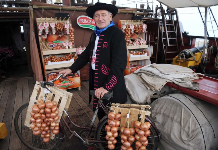 """French Francois Seite, President of the """"Onion Johnnies"""" association, poses with pink onions destined for Great Britain aboard the Etoile du Roy (Star of the King), a replica of an 18th-century sailing ship, on November 24, 2012 in Roscoff, western France. (Fred Tanneau/AFP/Getty Images)"""