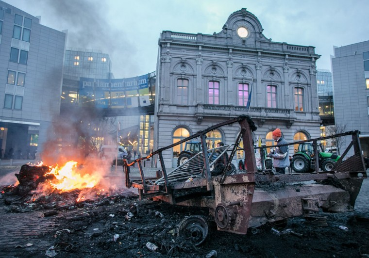 A man stands next to a charred trailer set on fire by dairy farmers in front of the EU Parliament at Place du Luxembourg, on the second day of a protest against falling milk prices in Europe in Brussels. The '1,000 tractors to Brussels' demonstration, which was organised by the European Milk Board (EMB), was expected to disrupt traffic in the Belgian capital until November 27, 2012 local traffic services said. (Olivier Vin/AFP/Getty Images