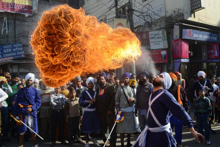 An Indian Sikh Nihang - warrior - performs a fire breathing act at a demonstration of gatka skills during a procession from Sri Akal Takhat to the Golden Temple in Amritsar on the eve of the 543rd birth anniversary of Sri Guru Nanak Dev. Guru Nanak was the founder of the religion of Sikhism and the first of ten Sikh Gurus. (Narinder Nanu/AFP/Getty Images)