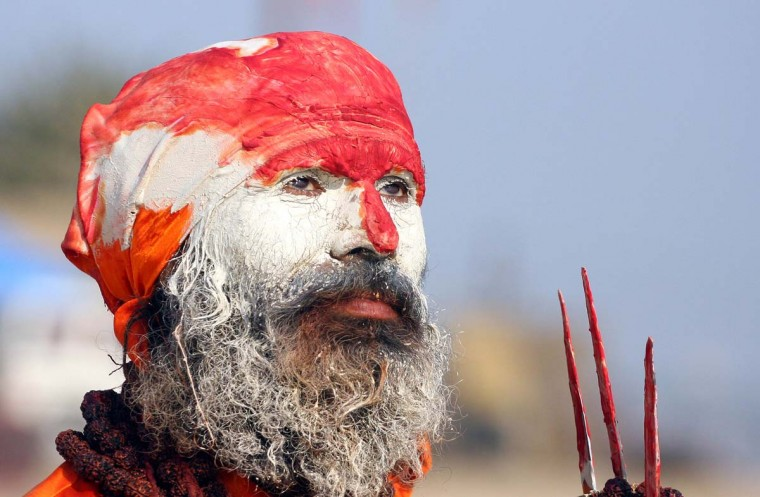 An Indian Hindu holy man, Sadhu, looks on from the banks of the Sangam, the confluence of the rivers Ganges and Yamuna in Allahabad. Allahabad, located in the north Indian state of Uttar Pradesh and where the Ganges, Yamuna and Saraswati rivers meet, is a focal point for Hindu pilgrims during The Maha Kumbh Mela, where millions of devotees gather to bathe every twelve years in the holy waters of the three rivers. (Sanjay Kanojia/Getty Images)