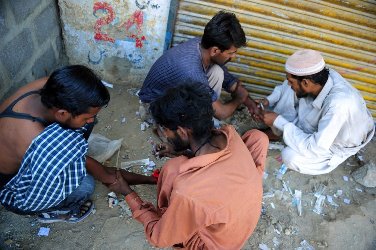Pakistani drug addicts inject heroin into each other on the roadside in Karachi on November 28, 2012. Pakistani cleric Abdul Khaliq Faridi used to think HIV/AIDS was a mortal sin. But today, he educates thousands about a disease on the rise in the deeply conservative Muslim country. He was among the first recruited by a government-sponsored project bringing clerics, the most influential segment of Pakistani society, into the fight against HIV/AIDS too commonly dismissed as depravity by ordinary people. (Rizwan Tabassum/AFP/Getty Images)