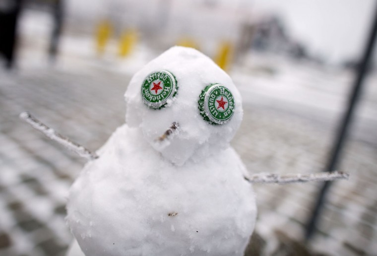 A small snowman has crown caps as eyes at the Grosser Feldberg mountain in the Taunus region, western Germany. Meteorologists forecast sinking temperatures and further snowfalls for the region. (Frank Rumpenhorst/AFP/Getty Images)