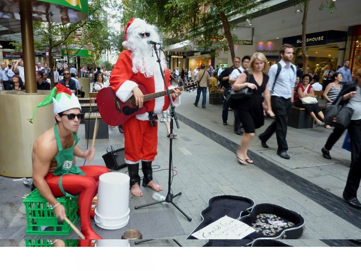 Buskers dressed up in Santa Claus suits perform in the downtown section of Sydney on December 23, 2010. (Amy Coopes/AFP/Getty Images)