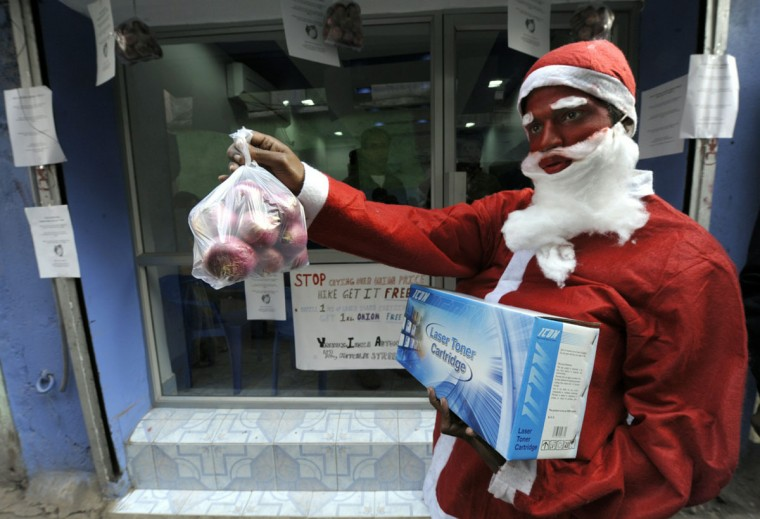 An salesman dressed up as Santa Claus holds a printer cartridge with a free onion bag offered for the purchase of a printer ink cartridge, to attract customer in a shop in Kolkata, India, on December 24, 2010. (Deshakalyan Chowdhury/AFP/Getty Images)