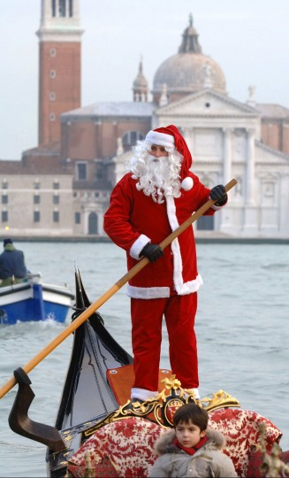 Gondolier Paolo Agostino, dressed as Santa Claus, crosses the famous Italian lagoon in front of the San Giorgio Maggiore island, December 2, 2005 in Venice. (Manuel Silverstri/AFP/Getty Images)