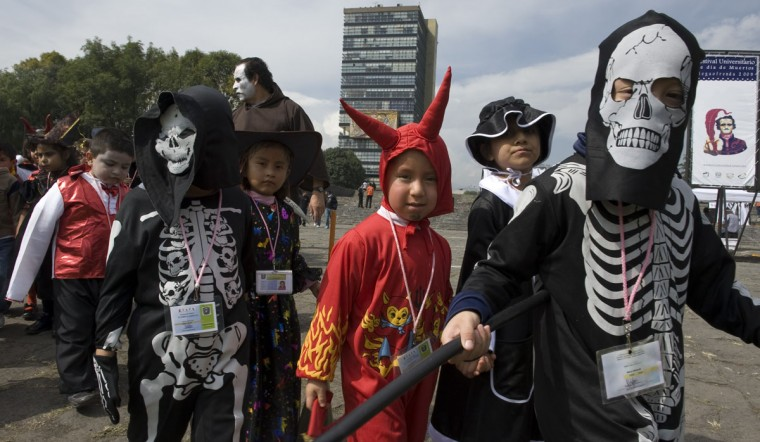 Children attending the kindergarten of the National Autonomous University of Mexico (UNAM), visit the Altars of the Dead set at the grounds of the UNAM in Mexico City on October 30, 2009. Mexicans celebrate the Day of the Dead on November 1 and 2 in connection with the Catholic holy days of All Saints' Day and All Souls' Day. Tradition includes building altars honouring their deceased relatives and this year, the UNAM dedicated the altars to US writer Edgar Allan Poe. (Omar Torres/AFP/Getty Images)