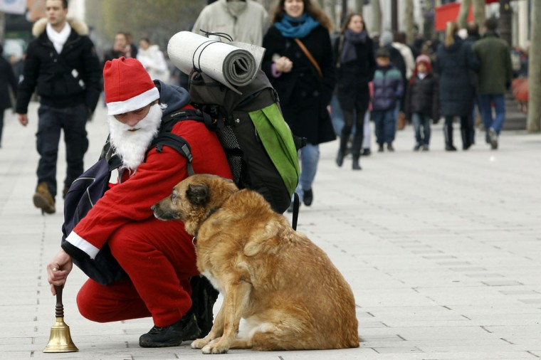 A homeless man dressed up as Santa Klaus looks at his dog in the Champs-Elysees in Paris on December 22, 2010 in Paris. (Joel Sagel/AFP/Getty Images)