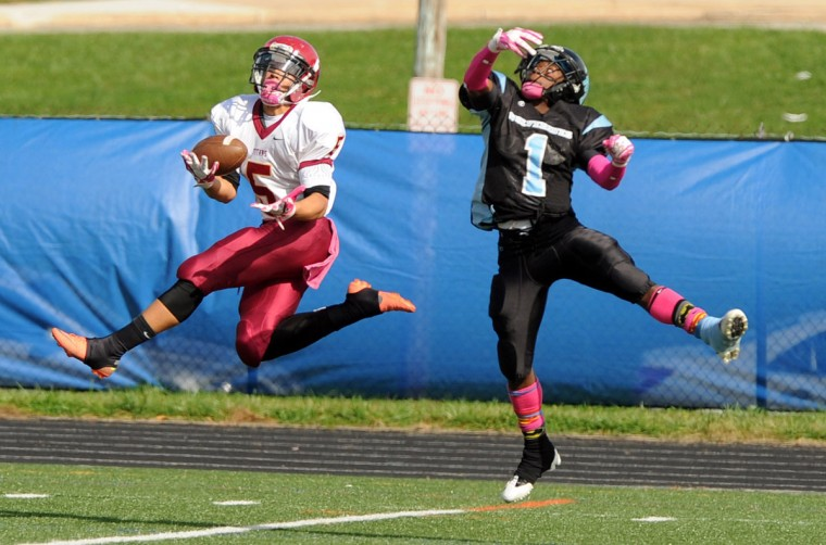 Donte Gross of New Town, left, makes a leaping catch on a ball out of the reach of Western Tech's Blair Awkward during a football game played at Lansdowne High School in Baltimore, on Saturday, Oct. 27. Gross ran the ball in for a touchdown on the play. (Brian Krista/Baltimore Sun Media Group)