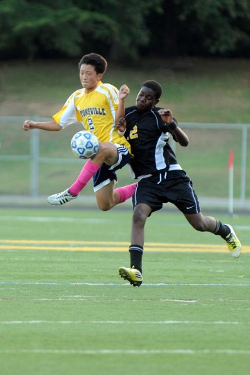 Daniel Kim of Catonsville, left, gets his knee on the ball as he's pushed from behind by Udo Udo of Parkville during a game at Catonsville High School in Catonsville on Wednesday, Oct. 10, 2012. (Brian Krista/Baltimore Sun Media Group)