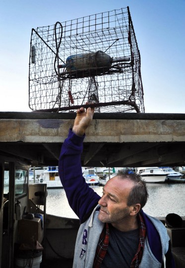 Kenny Foote, 49, moves a crab pot from his boat docked on Armstrong Creek. The season for catching mature female hard crabs was extended an extra week, through Nov. 17, due to days lost by watermen because of Hurricane Sandy. (Amy Davis/Baltimore Sun)