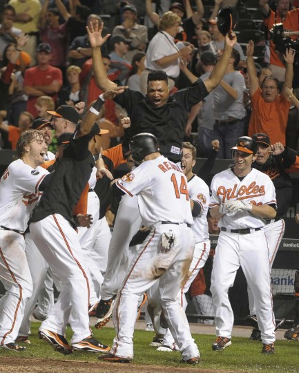 Baltimore Orioles teammates mob Nolan Reimold after he scored the winning run in the bottom of the ninth inning to beat the Boston Red Sox, 4-3, at Oriole Park at Camden Yards in Baltimore, Maryland, Wednesday, September 28, 2011. The loss eliminated the Red Sox from playoff contention. (Gene Sweeney Jr./Baltimore Sun)