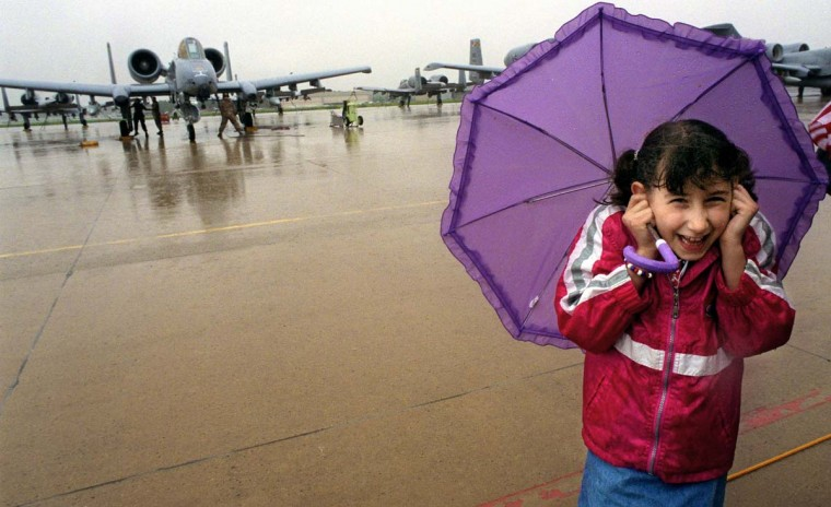 "Gloria Marino, 9, of Bel Air, covers her ears from the roar of the jet engines on her father's A-10, left. Lt. Col. Dan Marino, an A-10 ""Warthog"" pilot with the 104th Fighter Squadron arrived after returning from five months in Afghanistan along with seven other pilots and support crew. (Jed Kirschbaum/Baltimore Sun)"