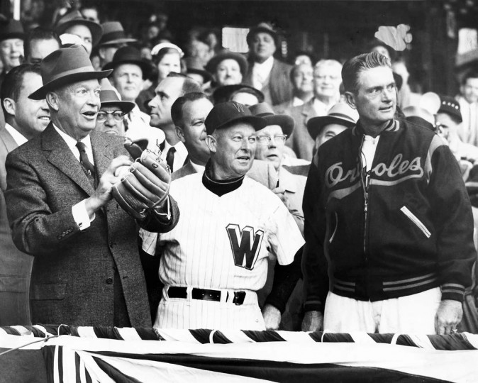 In April of 1957 President Eisenhower throws out the first pitch at opening day baseball game as Managers Chuck Dressen (Washington) and Paul Richards (Orioles) watch. The Baltimore Orioles vs. Washington Senators. (Robert F. Kniesche/Baltimore Sun)
