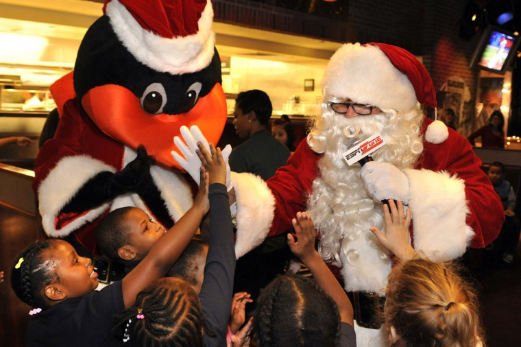 Santa, played by Rick Dempsey, high-fives the children in between Christmas songs with the Orioles Bird on December 9, 2009. First graders from Lakeland E.S. were invited to the ESPN Zone at the Inner Harbor for a holiday party with Orioles players, past and present. (Amy Davis/Baltimore Sun)