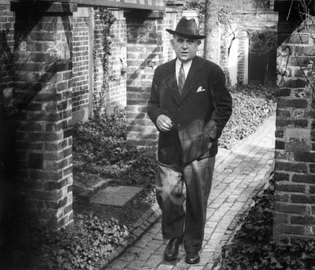 H. L. Mencken at home, in April of 1942 walking under grape arbor in his garden that he built. Mencken was a favorite subject of Kniesche. He took a number of portraits of the famous scribe. (Robert F. Kniesche/Baltimore Sun)