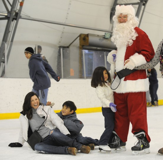 Kerry Madrid, from Catonsville, Maryland, takes a fall with her son, Nicholas Madrid, 7, while her daughter, Julia Madrid, 4, holds Santa's hand during 'Skating with Santa' at the Dominic 'Mimi' DiPietro Family Skating Center on December 17, 2011. (Lloyd Fox/Baltimore Sun)