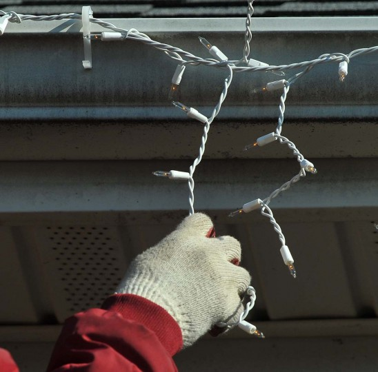 "Roberto Morales from the Frederick, Md, company ""The King of Christmas"", hangs a string of icicle lights, while decorating a Timonium home. (Gene Sweeney Jr./Baltimore Sun)"