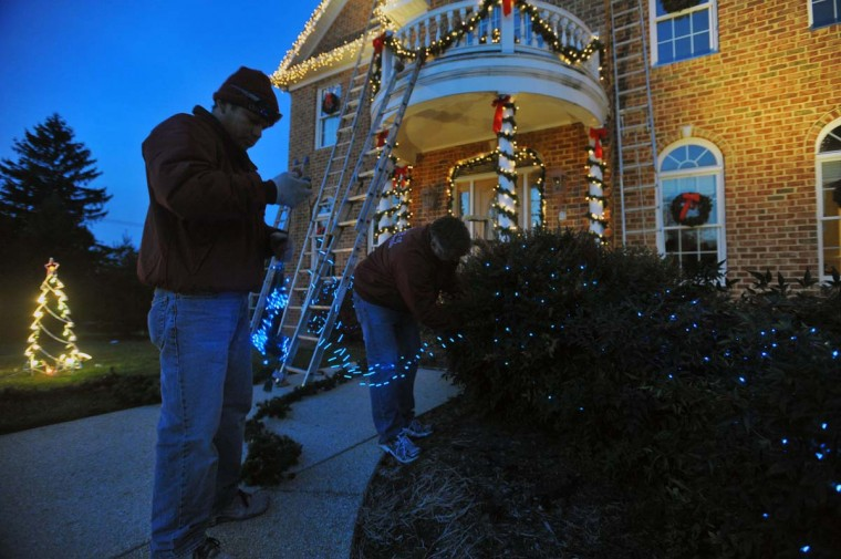 "Roberto Morales and Ron Alyman finishing the decoration installation by Ron's company ""The King of Christmas"", on this Timonium home. (Gene Sweeney Jr./Baltimore Sun)"