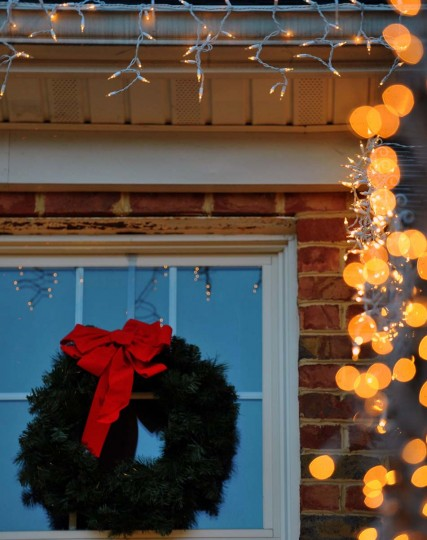 A Christmas wreath hangs on a window as lights begin to twinkle as dusk sets in during the installation. (Gene Sweeney Jr./Baltimore Sun)