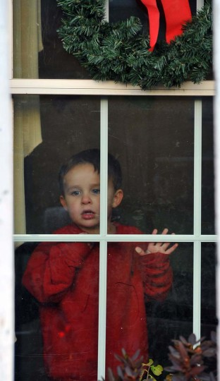 "3 year old, Hayden, watches from his home as decorations are installed by the Frederick, Md, company ""The King of Christmas"", on his Timonium home. (Gene Sweeney Jr./Baltimore Sun)"