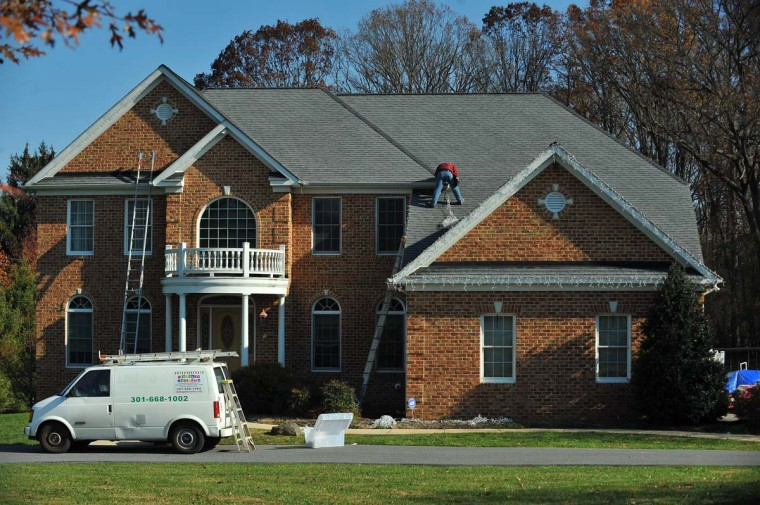 "Roberto Morales from the Frederick, Md, company ""The King of Christmas"", hangs a string of icicle lights, while decorating a Timonium home. This particular job will cost the home owner $2800.00, for installation followed by removal of all of the decorations in January. (Gene Sweeney Jr./Baltimore Sun)"