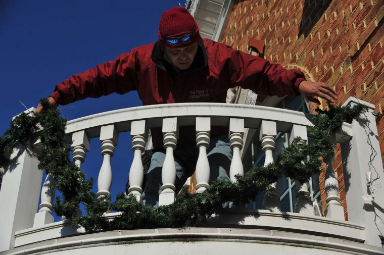 "Roberto Morales from the Frederick, Md, company ""The King of Christmas"", hangs garland, while decorating a Timonium home. (Gene Sweeney Jr./Baltimore Sun)"