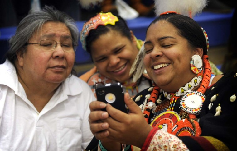 Georgie Sparks, Elyse Jackson and Dolly Lynch of Durham NC look at photos on Ms. Lynch's cell phone at the 38th annual Baltimore American Indian Center Powwow. They are part of the Haliwa-Saponi Lumbee Tribe. (Barbara Haddock Taylor/Baltimore Sun)