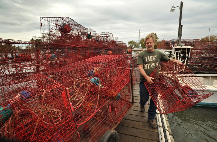 """On Armstrong Creek, waterman Harry Foote III, known as Captain Harry, stacks his crab pots on a dolly for storage after pulling them out of the water in advance of Hurricane Sandy. Foote was concerned that Hurricane Sally would shorten the crabbing season. """"Weather like this drives the crabs away. It wasn't a good season, and it will end early just like after Hurricanes Irene and Lee."""" (Amy Davis/Baltimore Sun)"""