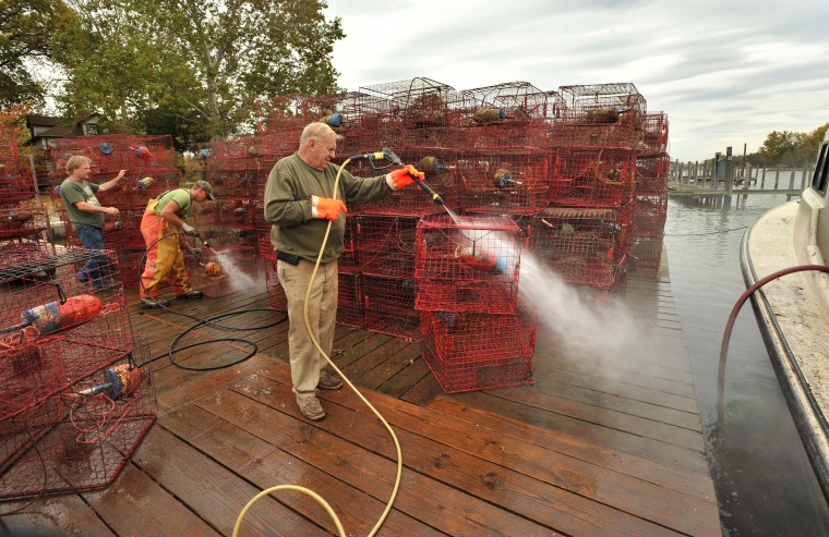 On Armstrong Creek, Tony Rill of Essex, at center, helps his friends, watermen Harry Foote III, left, and Dave Chiveral, second from left, hose down the crab pots the two watermen had pulled out of the water. Foote decided to pull up his crab pots before Hurricane Sandy hit eastern Baltimore County. (Amy Davis/Baltimore Sun)