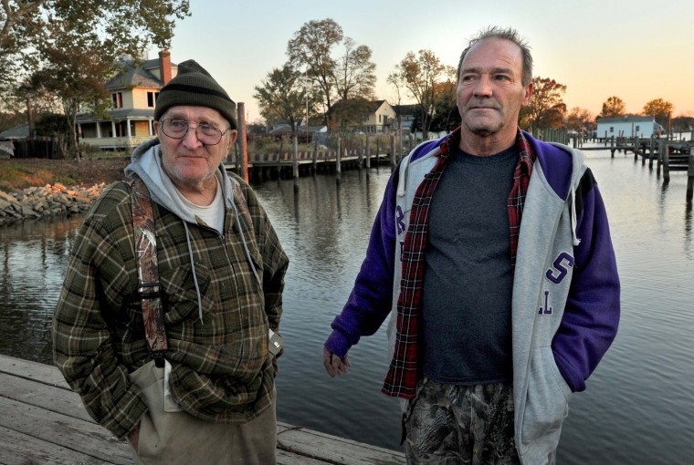 """Retired waterman Harry Foote, Jr., 74, left, with his son, Kenny Foote, 49, on the pier at Armstrong Creek at dusk. Two of Harry's three sons, Kenny and Harry III, are also watermen. Harry Foote Jr. said, """"You gotta be born into it almost."""" (Amy Davis/Baltimore Sun)"""