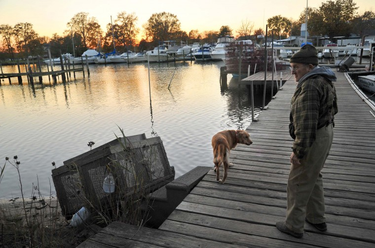 "Retired Waterman Harry Foote, Jr., 74, with his dog Sandy on the pier on Armstrong Creek at dusk. He said, ""Sometimes I go crabbing by myself, and sometimes with a helper."" (Amy Davis/Baltimore Sun)"