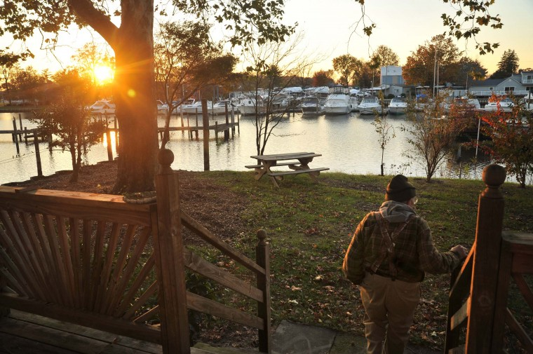 "Retired Waterman Harry Foote, Jr., 74, looking out at the sunset on Armstrong Creek from his home. He still loves being out on the water in the quiet of the morning. ""You gotta be born into it, though,"" he says. (Amy Davis/Baltimore Sun)"