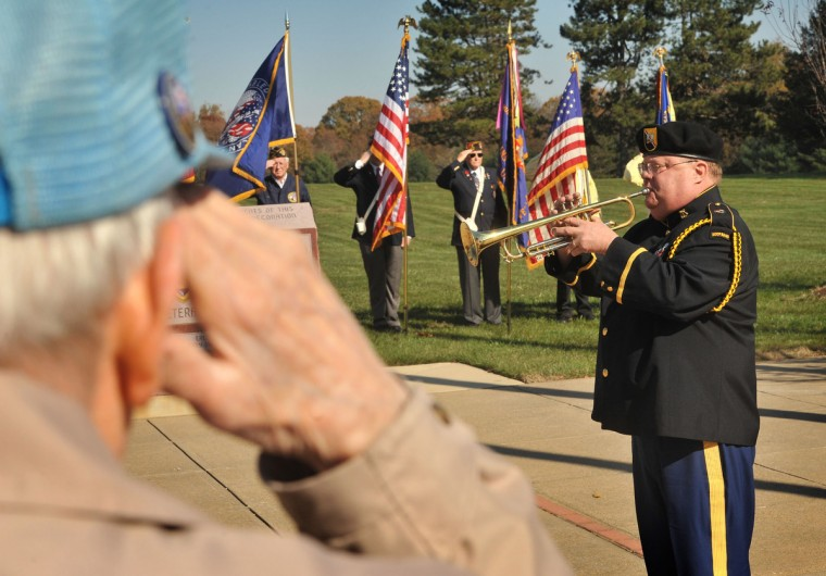 WWII veteran Clarence Schmitt of Crownsville, in foreground, salutes as bugler, (USA retired) Capt. Richard P. Barnes played taps during the wreath-laying portion of the Veterans Day ceremony held at the Crownsville Veterans Cemetery. (Amy Davis/Baltimore Sun)