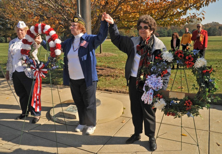Ladies Auxiliary representatives, from left, Janice Null (Military Order of the Purple Heart), Pat Schwarz (Disabled American Veteran) and Jeanne McDevitt (American Legion) performed the laying of the wreaths ceremony on Veterans Day at the Crownsville Veterans Cemetery. (Amy Davis/Baltimore Sun)